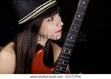 Brunette with a black hat holding red guitar