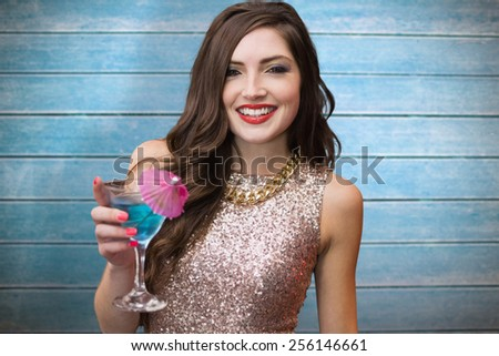 Brunette with cocktail against wooden planks