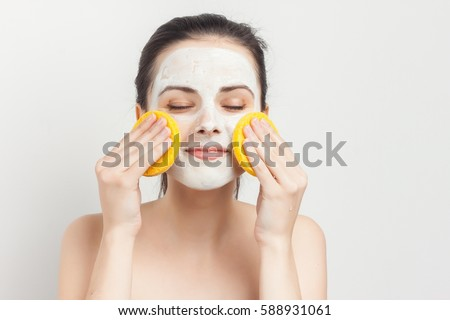 brunette with cream on her face and a sponge in his hands closed eyes.