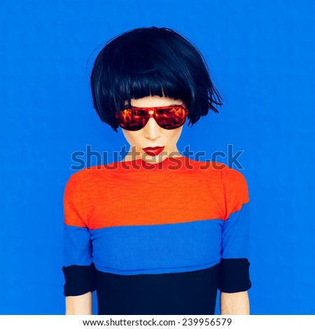 Brunette with fashionable Hairstyle and Sunglasses on  blue background - stock photo