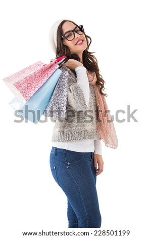 Brunette with glasses holding shopping bags on white background - stock photo