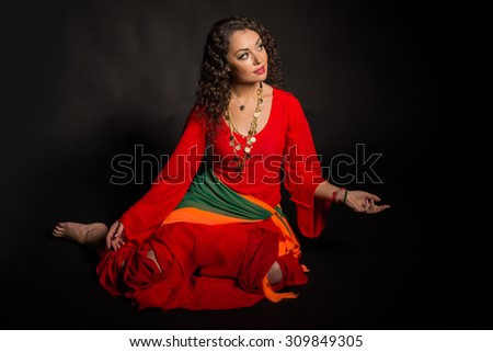 Brunette with gypsy dress. Traditional Gypsy women's accessories and dresses. Emotions and gypsy flavor. Gypsy on a black background.