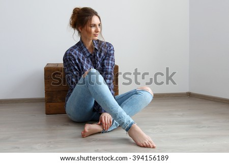 Brunette with hairstyle in the men's plaid shirt and blue jeans posing in studio