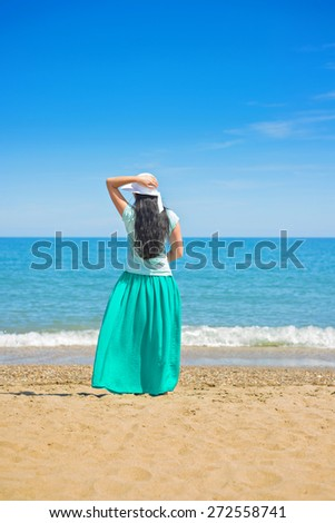 Brunette with long hair turned away on the sandy beach - stock photo