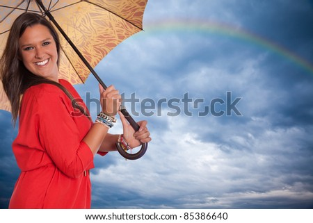 Brunette with umbrella smiling against a cloudy sky - stock photo