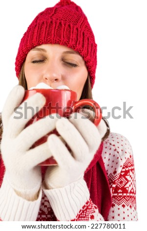 Brunette with winter clothes on holding mug of coffee on white background - stock photo