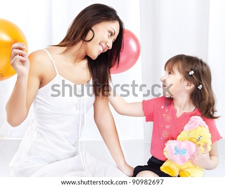 Brunette woman and child playing - stock photo
