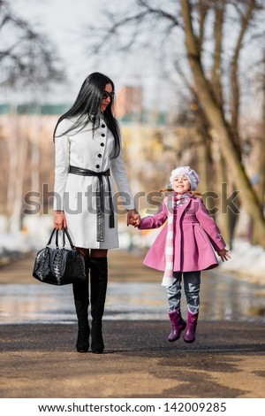 Brunette woman and jumping young girl at walkway (shallow dof) - stock photo