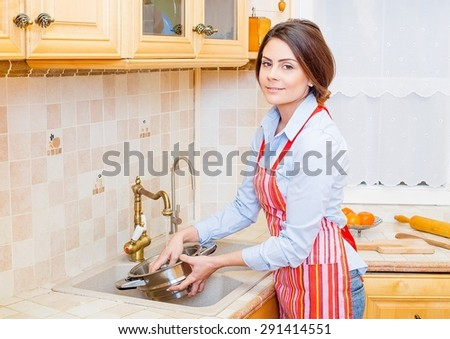 Brunette woman at home preparing food, washing vegetables. - stock photo