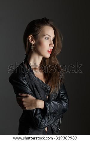Brunette woman at night, posing on dark grey background - stock photo