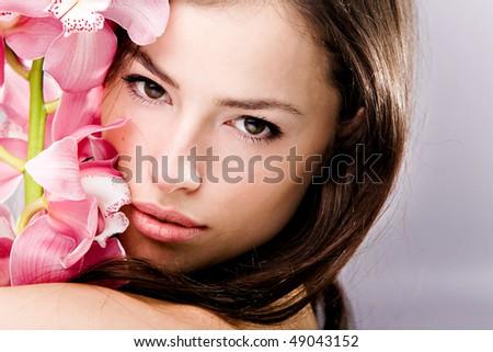 brunette woman beauty portrait with orchid, studio shot - stock photo