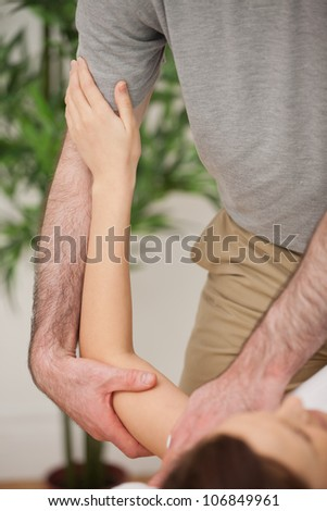 Brunette woman being manipulated by a doctor in a medical room - stock photo