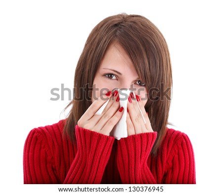Brunette woman blowing her nose into tissue isolated on white background