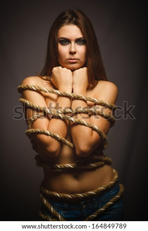 brunette woman bound with rope prisoner in jeans gray background emotion - stock photo