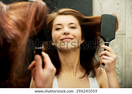 Brunette woman brushing hair in front of bathroom mirror. - stock photo