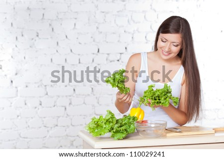 brunette woman cooking fresh salad over white brick wall
