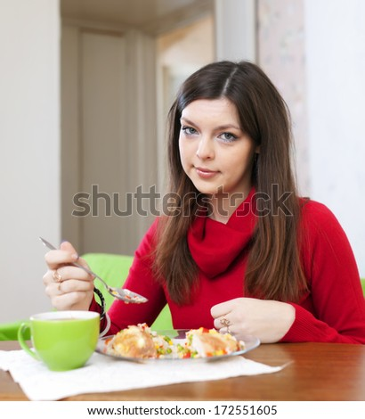 Brunette woman eats chicken with vegetables at home - stock photo