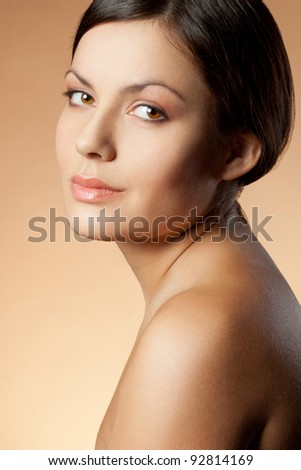 brunette woman face vertical portrait over skintone background - stock photo