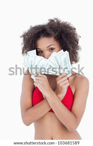 Brunette woman hiding her face behind two fans of notes against a white background