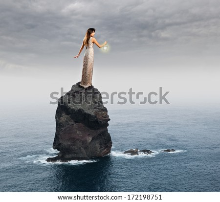 brunette woman holding a lantern on a rock in the sea