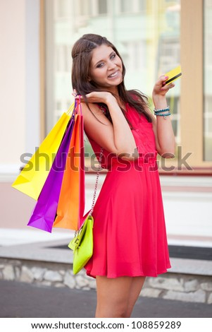 brunette woman holding credit card and bags - stock photo