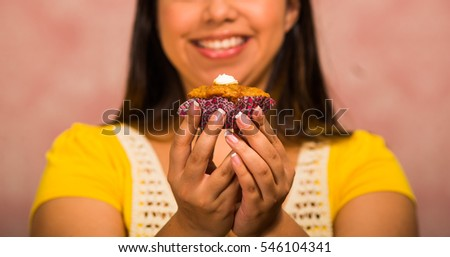 Brunette woman holding delicious brown colored muffin with cream topping, big smile and ready to take a bite, pastry concept