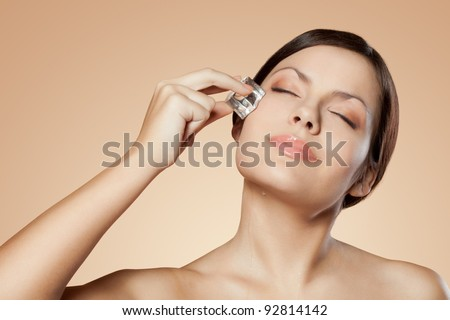 brunette woman holding ice cube on her face - stock photo