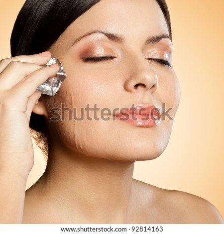 brunette woman holding ice cube on her face, closeup portrait