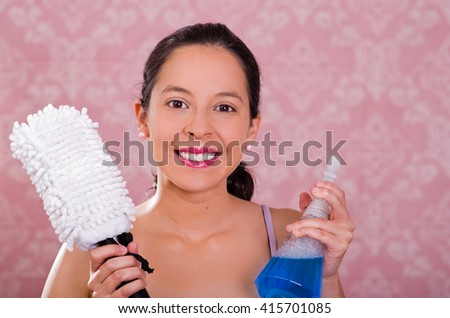 Brunette woman holding spray bottle of blue liquid and white fluffy cleaning brush while smiling to camera, pink background - stock photo