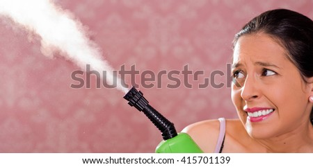 Brunette woman holding steam cleaner machine and vapor coming out, scary facial expression, pink background - stock photo