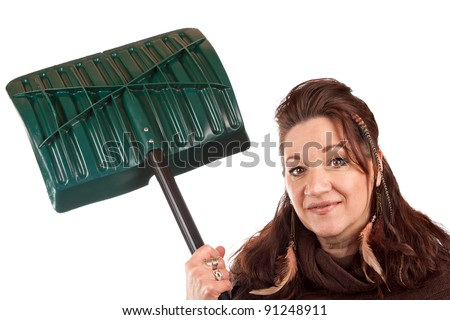 Brunette woman holding up her snow shovel isolated over a white backdrop. - stock photo