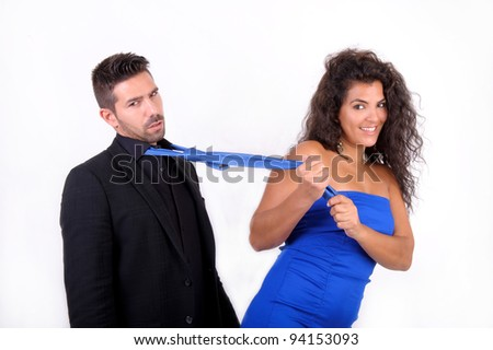 brunette woman in blue dress dragging a man with his blue tie - stock photo