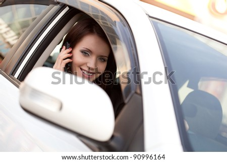 brunette woman in car with mobile phone