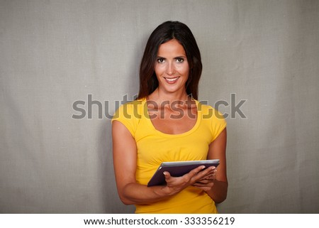 Brunette woman in casual clothing smiling while holding tablet - copy space - stock photo