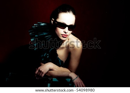 brunette woman in elegant dress and with sunglasses, studio shot - stock photo