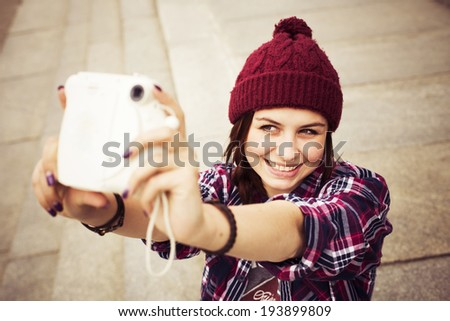 Brunette woman in hipster outfit sitting on steps and taking selfie on retro camera on the street. Toned image - stock photo