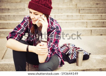 Brunette woman in hipster outfit sitting on steps and talking on the phone on the street. Toned image. Copy Space - stock photo