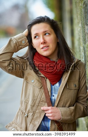 Brunette woman in red scarf and khaki jacket - stock photo