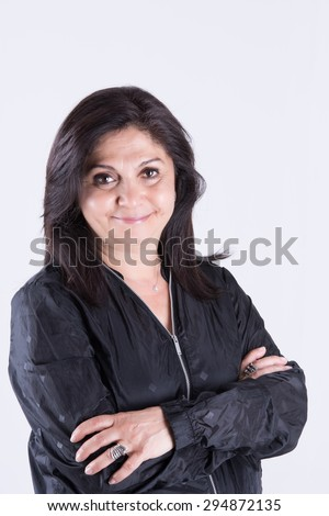 Brunette woman in 50s with crossed arms and black sports jacket half body shot - stock photo