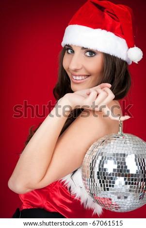 brunette woman in santa costume holding disco ball - stock photo