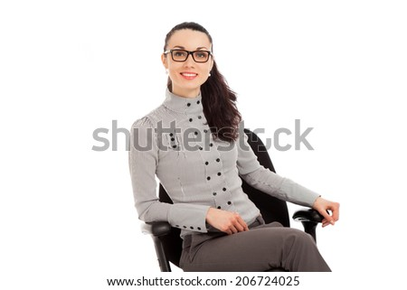 brunette woman in shirt and trousers sitting in office chair over white background - stock photo