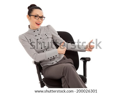brunette woman in shirt and trousers sitting in office chair presenting something over white background - stock photo