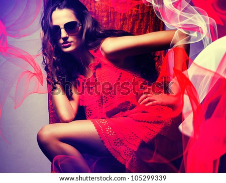 brunette woman in sunglasses and red dress around red and white fabric - stock photo