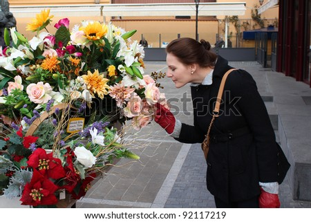 Brunette Woman In Winter Clothing Smelling Colorful Flowers