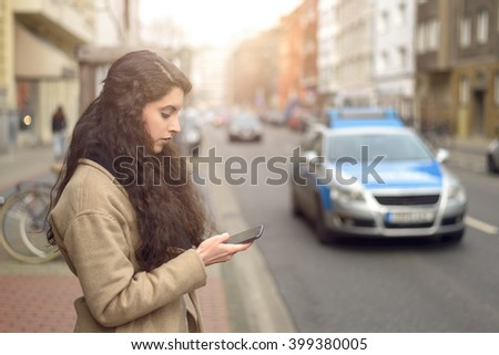 Brunette woman is distracted with texting while standing by busy street is unaware of oncoming traffic - stock photo