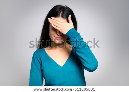 brunette woman is sad and crying, close-up isolated on a gray background
