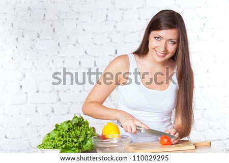 brunette woman looking at camera and cutting  fresh tomato over white brick wall