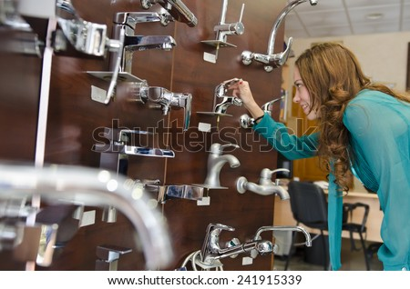 brunette woman looking faucets at plumbing store - stock photo