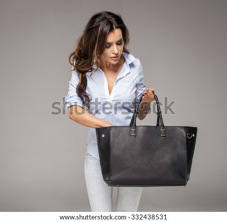 Brunette woman looking for something in her bag - stock photo