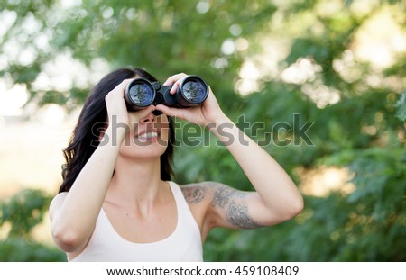 Brunette woman looking through the binoculars while strolling through a lush forest - stock photo